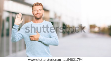 young blonde man smiling confidently while making a sincere promise or oath, solemnly swearing with one hand over heart.