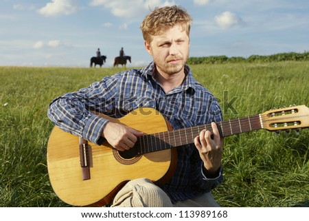 Young blonde man strumming a guitar while sitting in an open grassy field with horse riders on the skyline