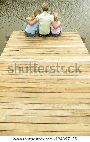 Young blonde mother and her two daughters sitting close together on the end of a wooden jetty alongside a lake.