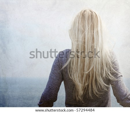 Young blonde near the sea. Photo in vintage colored image style.