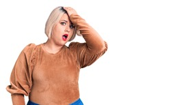 Young blonde plus size woman wearing casual sweater surprised with hand on head for mistake, remember error. forgot, bad memory concept.