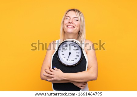Young blonde Russian woman over isolated yellow background with weighing machine Photo stock ©