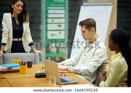 young blonde serious guy discussing problems with his coworkers in the office room with modern interior. close up side view photo.unpleasant situation, failure concept stock photo