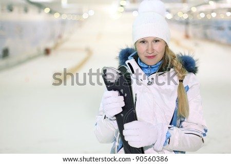 Young blonde smiling woman dressed in white sports clothes stands and keeps skis in indoor ski