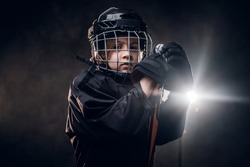 Young blonde sporty boy, ice hockey player, posing in a dark studio for a photoshoot, wearing an ice-skating uniform while wearing his helmet, holding hands on hockey stick and being quiet and calm