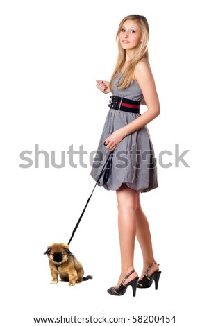 Young blonde walking over her pekingese puppy. Isolated on white