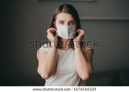 Young blonde white european blue-eyed woman at home on quarantine with medical mask on gray background. Coronavirus, illness, infection, quarantine, surgical bandage.