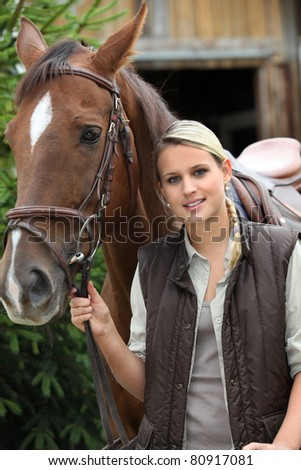 young blonde woman and a horse in front of a stable