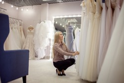 young blonde woman chooses a wedding dress in a wedding salon. The bride-to-be is looking for the perfect dress for herself. Dress store, large assortment