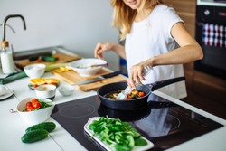 Young blonde woman cooking in the kitchen. Healthy Food. Dieting Concept. Healthy Lifestyle. Cooking At Home. Prepare Food