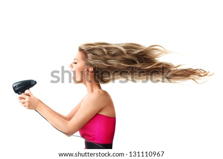 Young blonde woman drying long hair with electric fan isolated on white background