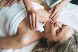 Young blonde woman enjoys facial massage with microcurrent facial massager in the spa, treat yourself. Professional body care