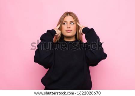 young blonde woman feeling confused or doubting, concentrating on an idea, thinking hard, looking to copy space on side against flat wall
