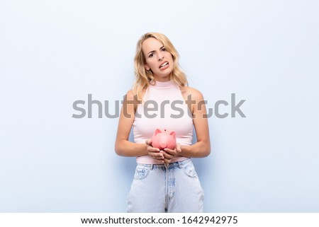 young blonde woman feeling puzzled and confused, with a dumb, stunned expression looking at something unexpected holding a piggybank