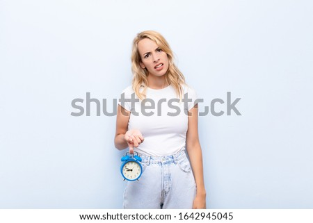 young blonde woman feeling puzzled and confused, with a dumb, stunned expression looking at something unexpected holding a clock