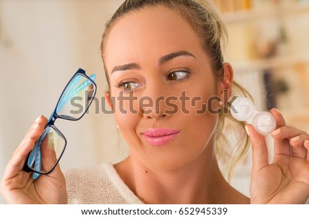 Young blonde woman holding contact lens case on hand and holding in her other hand a blue glasses on blurred background., eyesight and eyecare concept #652945339