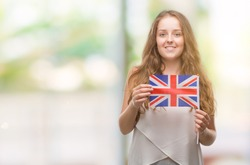 Young blonde woman holding flag of UK with a happy face standing and smiling with a confident smile showing teeth