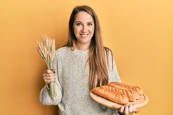 Young blonde woman holding homemade bread and spike wheat smiling with a happy and cool smile on face. showing teeth.