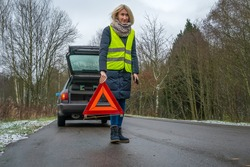 Young blonde woman in a winter down jacket in a yellow vest holds an emergency stop sign an orange triangle near a car with an open trunk
