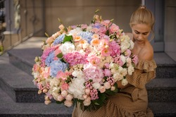 young blonde woman in beige dress carefully holds in her hands huge bouquet of different flowers