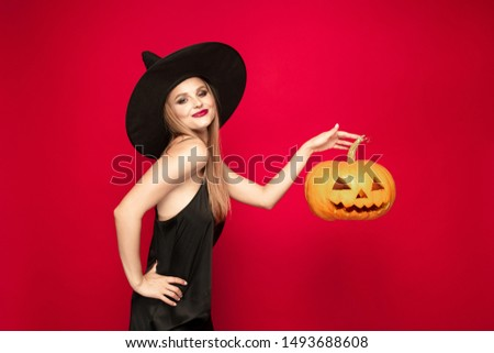 Young blonde woman in black hat and costume on red background. Attractive caucasian female model. Halloween, black friday, cyber monday, sales, autumn concept. Copyspace. Holds pumpkin.