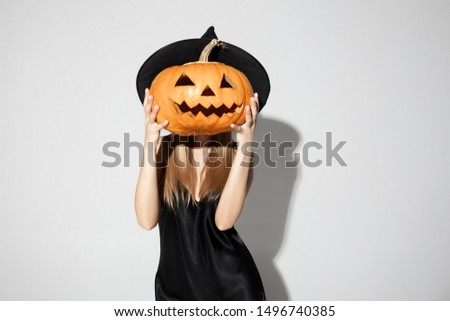 Young blonde woman in black hat and costume on white background. Attractive caucasian female model posing. Halloween, black friday, sales, autumn concept. Copyspace. Holding a pumpkin as a head.
