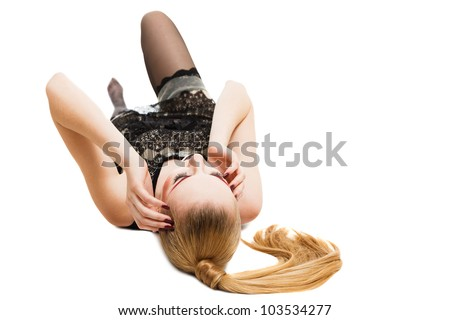 Young blonde woman in black mini dress lying down on floor