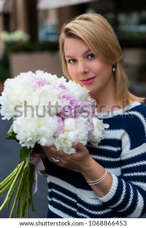 Young blonde woman in blue dress with peonies bouquet outdoors at city street #1068866453