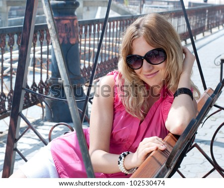 Young blonde woman in pink  sitting on a swing outdoors