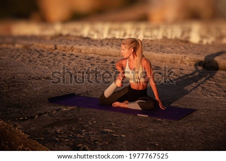 Young blonde woman in sportswear performs yoga asanas, exercises on the seashore at sunrise. The girl goes in for sports, works out breathing, meditates, performs Dove pose. Healthy mind in a fit body Photo stock ©