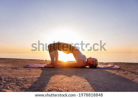 Young blonde woman in sportswear performs yoga asanas, exercises on the seashore at sunrise. The girl in sports, works out breathing, meditates, performs Half Bridge Pose. Healthy mind in fit body Photo stock ©