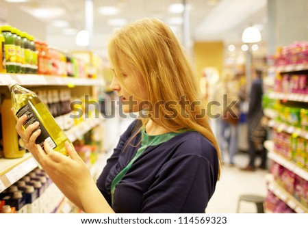 Young blonde woman in the supermarket is reading inscription on the juice bottle