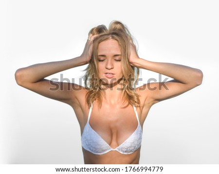 young blonde woman in white bra demonstrating her perfect body with silky smooth skin. Lingerie model, sensual body. bra. Sexy  girl wearing white swimsuit  isolated on gray background. closed eyes