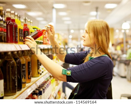 Young blonde woman is choosing juice in the supermarket