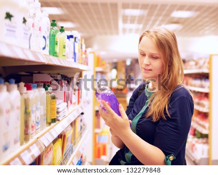 Young blonde woman is reading inscription on the cleaner bottle in the supermarket