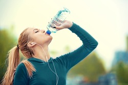 Young blonde woman is relaxing after jogging and drinking water.