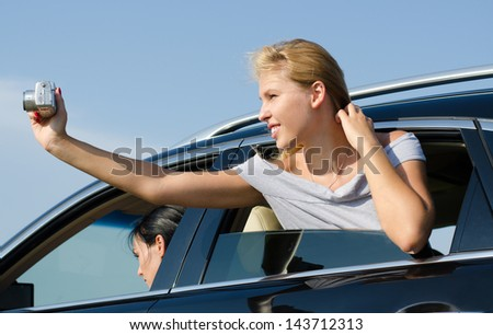 Young blonde woman leaning out of the passenger window taking photos from a car