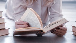 Young blonde woman lying down and leafing through the book. Woman reading a book. Image without a face, hands holding a book. Learning concept, love of literature.