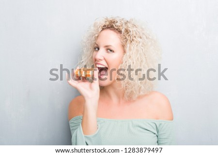 dbf629c29ca Young blonde woman over grunge grey background eating belgian waffle with a confident  expression on smart