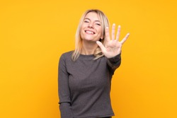 Young blonde woman over isolated yellow background counting five with fingers