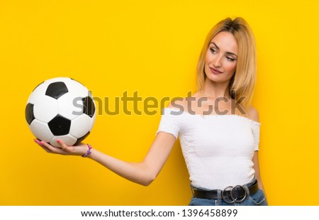 Young blonde woman over isolated yellow wall holding a soccer ball