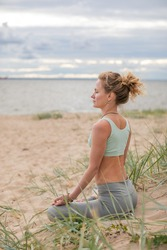 Young blonde woman practicing yoga on the coast. Professional trainer meditating in beach dune by seaside.