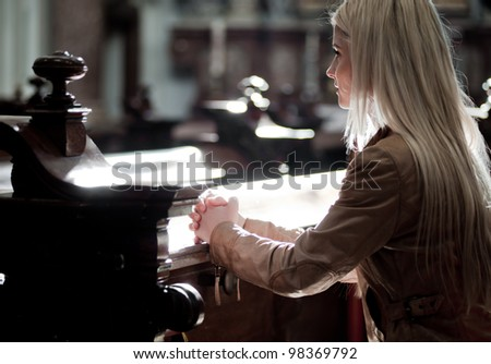 Young blonde Woman praying in the Church