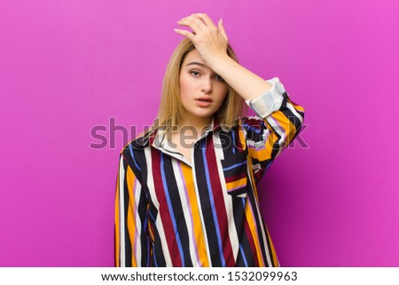 young blonde woman raising palm to forehead thinking oops, after making a stupid mistake or remembering, feeling dumb against purple wall