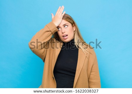 young blonde woman raising palm to forehead thinking oops, after making a stupid mistake or remembering, feeling dumb against flat wall
