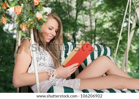 Young blonde woman reading a book resting in lounge