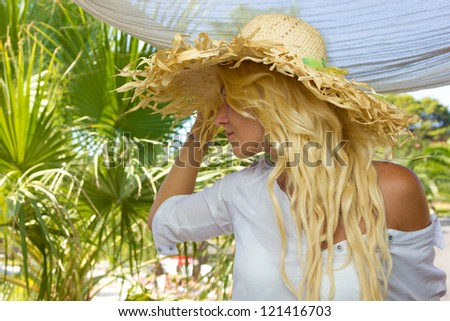 Young blonde woman relaxing at summer resort