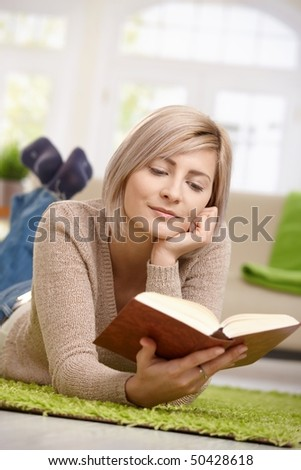 Young blonde woman relaxing on floor at home reading book. Copyspace above.