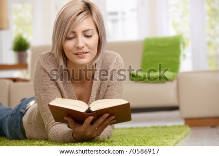 Young blonde woman relaxing on floor at home reading book. Copyspace on right.?