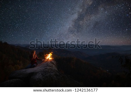 Young blonde woman resting near bonfire outdoor at starry night. Milky Way at mountains. Camp fire on a top of a mountain. Burning fire at dusk on the mountains. Night colorful landscape #1242136177